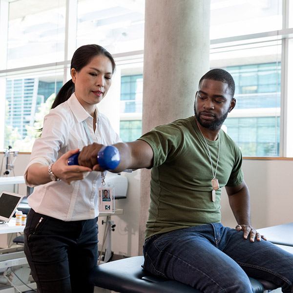 Serious army soldier with injury uses a hand weight during a physical therapy session. A female physical therapist is helping him with an exercise.